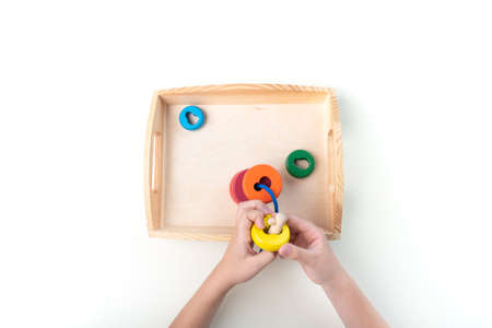 Montessori material. Hand of a child. White background. Toddler education. Study of mathematic and letter. School and kindergarten. Reklamní fotografie - 162164053