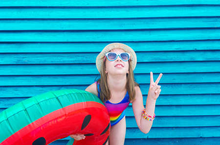 Girl with an inflatable watermelon. Wooden background. Active holidays with family on the beach pool. Emotional kid