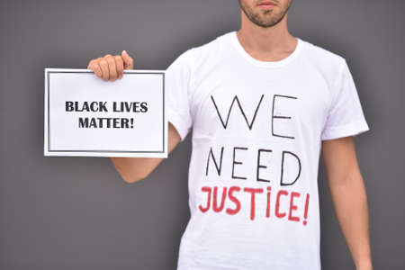 Man is holding paper with words Black lives matter in front of grey wall.