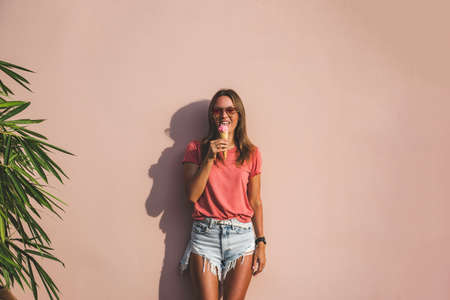 Model girl in jeans shorts and pink t-shirt licking ice cream on pink background