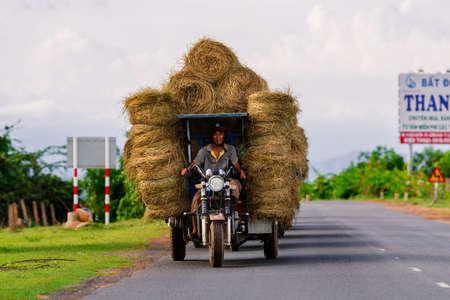 Dalat, Lam Dong, Vietnam - July 2020: An Vietnamese man transports stacks of hay on a three wheeler vehicle
