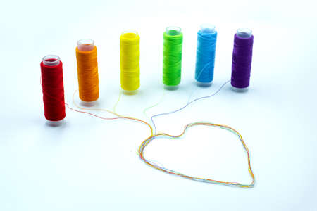 Colourful thread spools with a heart shape isolated on a white background. Lgbt and love symbol. Lesbian, gay, bisexual, transgender community rights support concept.