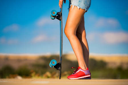 Stylish fit and sporty woman with beautiful tanned legs and in red sneakers holds longboard on shiny summer day . Outdoor activities. Street culture. Stock fotó