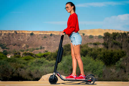 Cute woman in red hoodie and blue shorts riding electric scooter in sunny summer day. Summertime fun. Stock fotó - 155446297