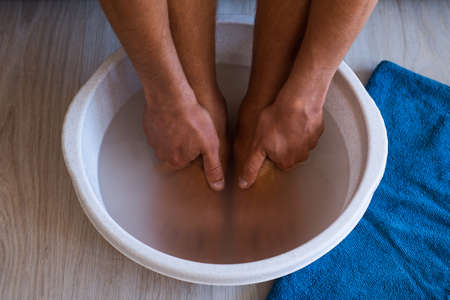 Male put hands and feet in bath with hot water and baking soda at home. Homemade bath soak for dry feet skin