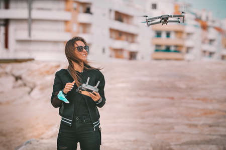 Pretty modern smiling woman pilot in dark stylish clothes flying drone with strong wind in city. Fly drone with permission. Outdoors hobby.