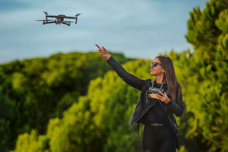 Cute modern smiling woman pilot in dark stylish clothes flying drone in park at sunset. Outdoors hobby.