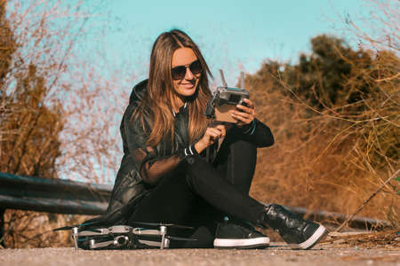 Young modern woman in stylish dark clothes and sunglasses preparing to start flying drone on sunset or sunrise.