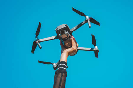 Woman hand holding drone or quadcopter isolated on the blue sky background.