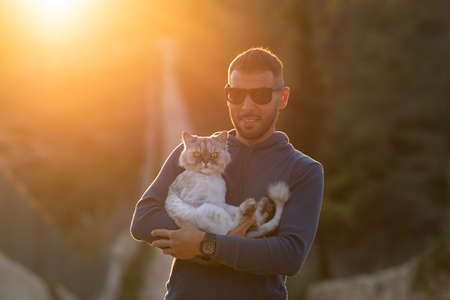 Man holds in hands his lovely purebred cat outside on the sunset. Pet with owner