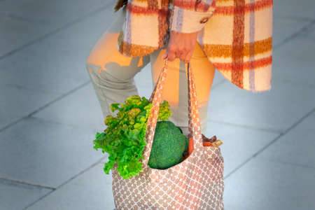 Woman with eco reusable textile grocery bag with vegetables. Healthy plant based diet. Zero waste, plastic free concept