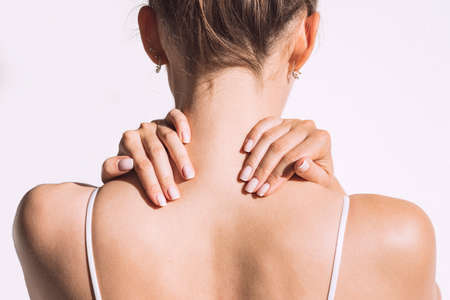 Closeup shot of woman from back having neck or shoulder pain. Injury or muscle spasm. Back and spine disease. Female massaging her neck. Health care and medical concept Standard-Bild