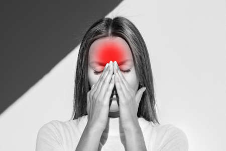 Woman feeling unwell, painful headache because of sinus ache, sinusitis, sinus pressure. Sad woman holding her nose and head because sinus pain. Coronavirus symptoms