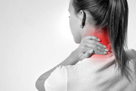 Closeup shot of woman suffering from neck pain. Female massaging her neck. Health care and medical concept