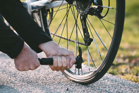 Close-up of a man pumping bicycle wheel on the street. Man inflates bicycle wheel using a pump. Pumping air into an empty wheel of bike