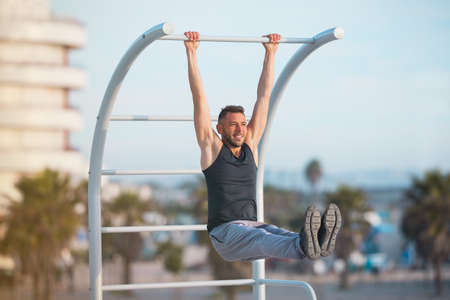Fitness man exercising his abs with hanging leg raises. Man doing pull-ups in the street. Exercising on wall bars with his legs up. Doing calisthenics, exercising outdoors. Healthy lifestyle concept.