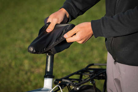 Man putts black rain cover on the bicycle saddle. Bicycle waterproof seat cover. Bike saddle care
