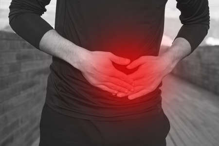 Man in black sports clothes with stomach side stitch or cramps during running. Athlete suffering from side pain