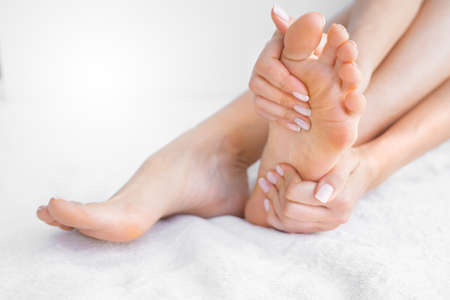 Young woman on a white background massaging her painful foot to relieve pain. Feet pain. Woman suffering from podalgia. Health care and spa concept Stock Photo