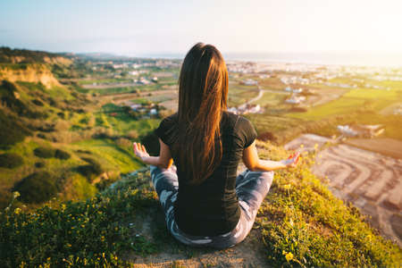 Woman practices yoga and meditates on the top of the mountain with beautiful view on the city and ocean at sunset. Woman sitting in easy pose or sukhasana with mudra. Relaxation, harmony with nature