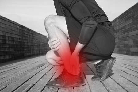 Running and workout injuries. Athlete suffering from ankle pain or achilles injury. Ankle twist sprain accident