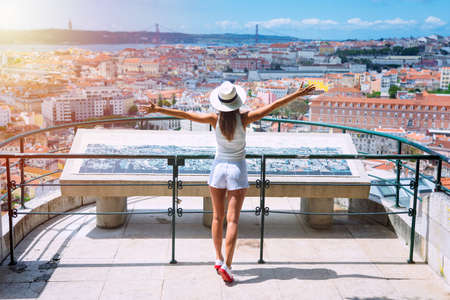 Tourist attractions. Young carefree woman tourist in white clothes and hat with open arms enjoying the view of Lisbon city from viewpoint at sunny summer day. Travel, vacation and holidays concept.