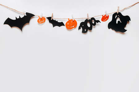 Happy halloween holiday concept. Bats, pumpkins and ghosts on rope with clothespin on white isolated background