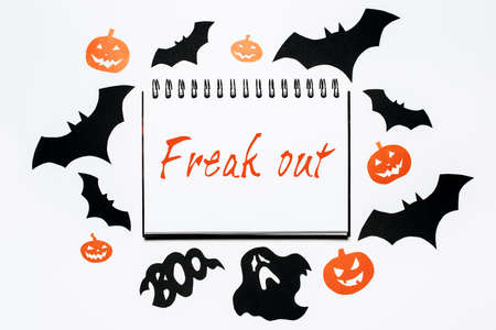 Happy halloween holiday concept. Notepad with text Freak out on white background with bats, pumpkins and ghosts