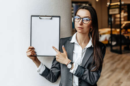 The woman shows information on the tablet. Place for advertising. Business concept. The girl in glasses holds the documents and explains the information. White blank sheet of paper.