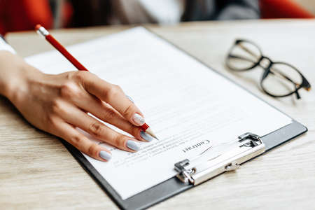 Young girl office worker or business lady signs documents. Concentrated businesswoman working with papers. Business concept Banque d'images
