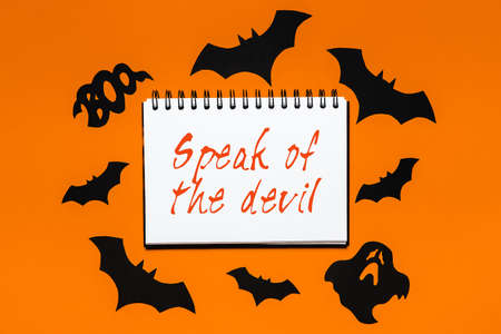 Happy halloween holiday concept. Notepad with text Speak of the devil on white and orange background with bats, pumpkins and ghosts