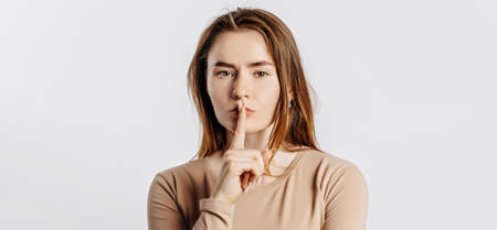 Shh gesture. Young beautiful girl frowning and holding a finger to her lips on a white isolated background. A woman asks to be silent, a place for advertising. Negative brunette in a beige jumper.