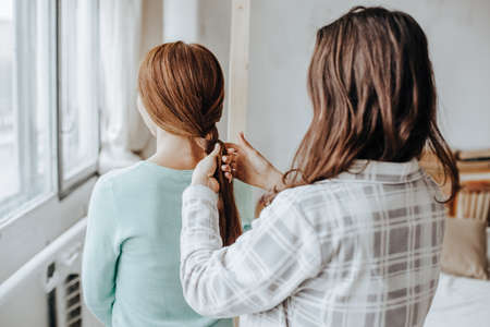 Two girls braid their hair at the window. Woman makes a braid to her friend. Hair weaving hairstyles. Girlfriend braids her hands with ringlets. Hair care Standard-Bild