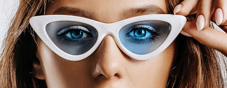 Beautiful young brunette girl with green eyes with fashion makeup. The woman in blue sunglasses seriously looking at the camera. Beauty concept. Stok Fotoğraf