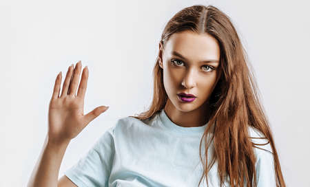 Hey. Beautiful young girl with a gesture greets, raises her hand with her palm to the camera on an isolated gray background. Brunette woman with fashion makeup with purple lips seriously looking