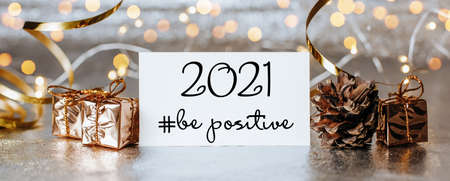 Merry christmas and merry new year concept with gift boxes and greeting card with text 2021 be positive