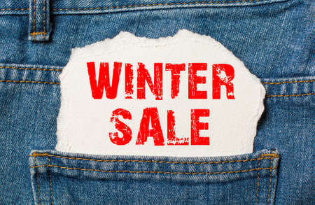 winter sale on white paper in the pocket of blue denim jeans