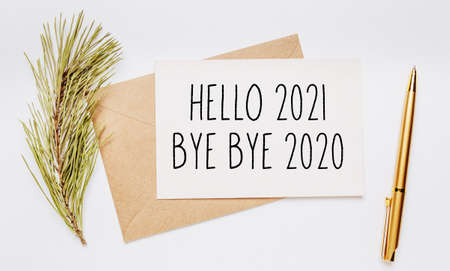 hello 2021 bye bye 2020 note with envelope, spruce branch and gold pen on white background. merry christmas and New Year concept Stockfoto