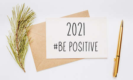 2021 be positive note with envelope, spruce branch and gold pen on white background. merry christmas and New Year concept Foto de archivo