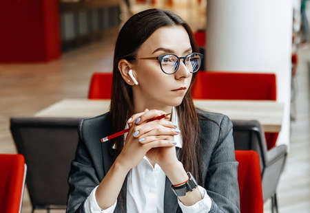 Girl works on a laptop in the workplace. Successful business woman creates a startup and makes decisions.
