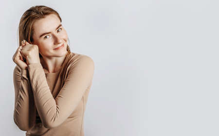 Young beautiful girl smiles and is touched and holds two hands at the face on a white isolated background. A woman points to an idea, a place for advertising. Positive cute brunette in a beige jumper