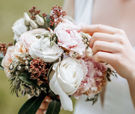 Girl bride holding a wedding bouquet of flowers