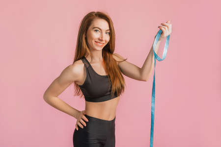 Fitness girl smiling and posing hold measure tape in black sportswear on a pink background. Slim woman with a beautiful athletic body and tanned skin