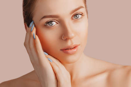 Beautiful sensual young girl with clean skin on a beige background with a mockup. Topless woman in a towel. The concept of spa treatments, natural beauty and care, youth, cream and mask, freshness Standard-Bild