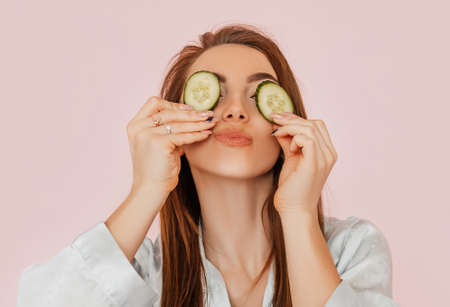 Girl make homemade face beauty masks. Cucumbers for the freshness of the skin around the eyes. Woman take care of youthful skin. Model laughing and having fun in spa on pink background Standard-Bild