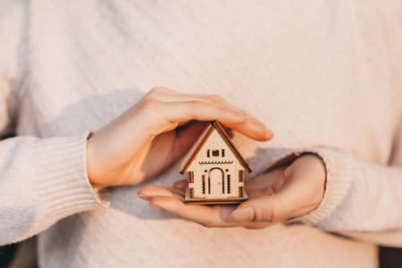 Woman holding a wooden house with her hands with the sun on a light pink background. Sweet home 版權商用圖片