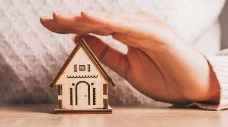 Woman holds and protects a wooden house with her hands with the sun on a light pink background. Sweet home 版權商用圖片
