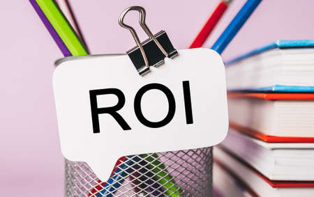 Text ROI on a white sticker with office stationery background. Flat lay on business, finance and development concept