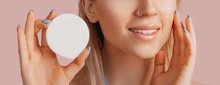 Girl make face beauty masks. Anti-wrinkle cream for the freshness of the skin around the eyes. Woman take care of youthful skin. Model laughing and having fun in spa on pink background