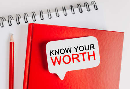 Text KNOW YOUR WORTH on a white sticker with office stationery background. Flat lay on business, finance and development concept
